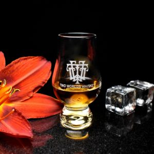 Two Worlds Whiskey Wee Glencairn Distillers Glass on black background with orange flower and ice cubes