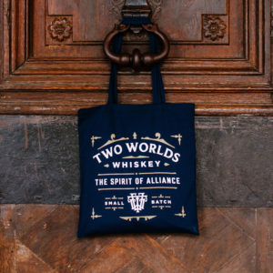 Two Worlds Whiskey canvas tote bag hanging on a door